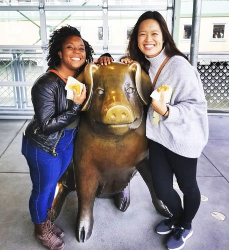 View of the author and her friend taking a picture with Billie the bronze pig