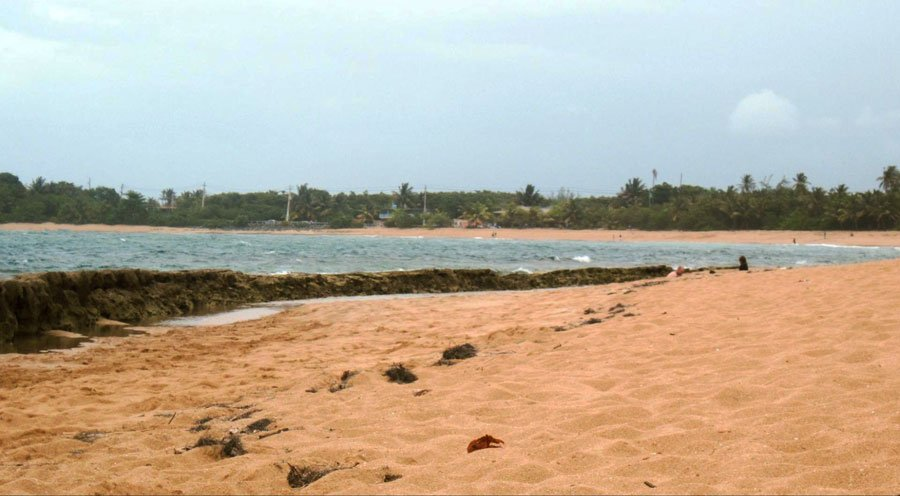 View of sand by the sea in Piñones