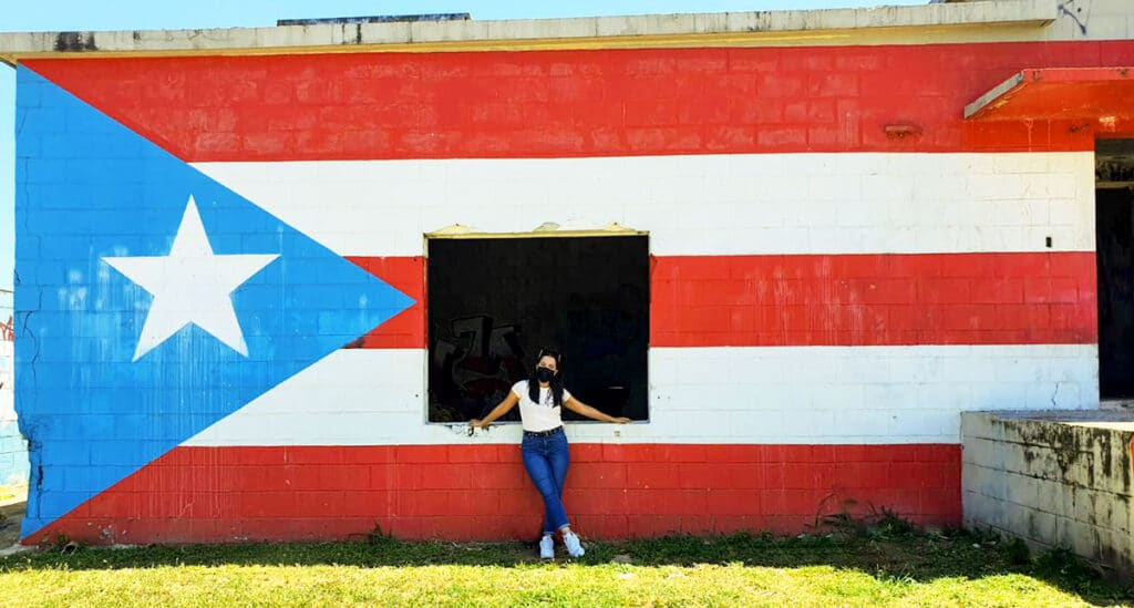 View of the author with a flag of Puerto Rico mural in the background