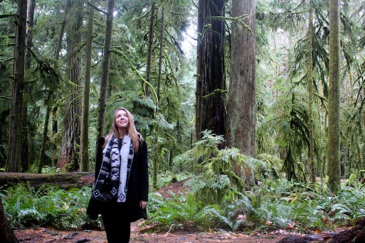 Taylor stands in the middle of Cathedral Grove, British Columbia Canada, surrounding by rainforest