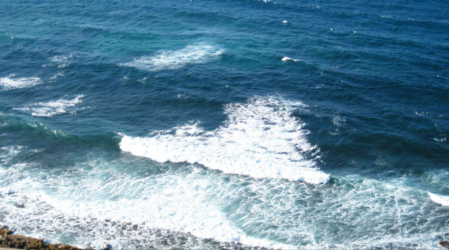 View of some small waves from the blue water of Playa Pena