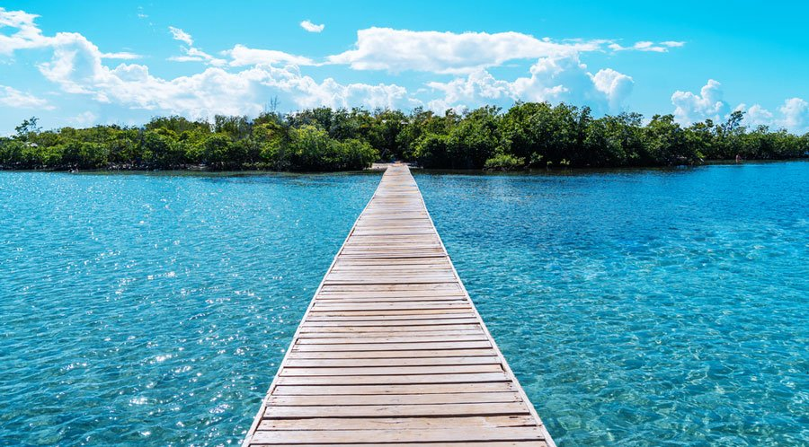 View of the clear water in Cayo Aurora and a wooden pathway
