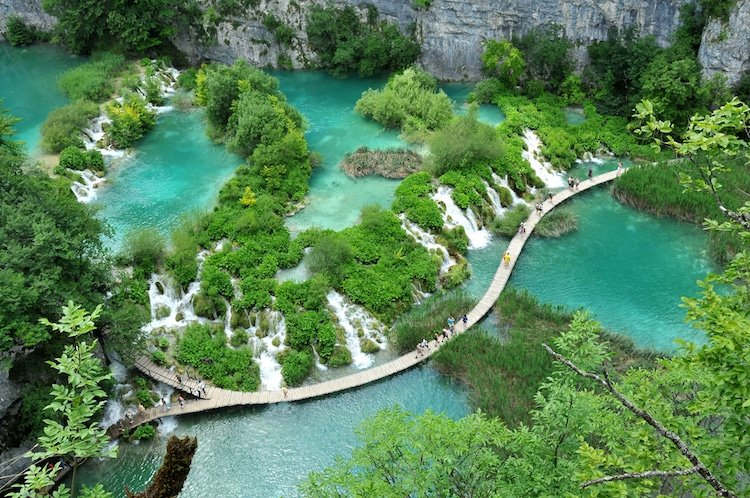A boardwalk runs through the turquoise lakes and waterfalls of Plitvice Lakes National Park, Croatia
