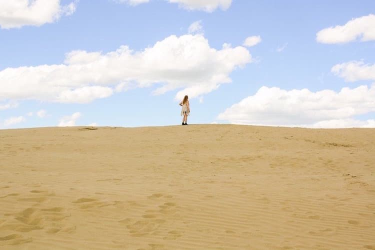 Taylor stands on top of a sand dune beneath blue skies in the Great Sandhills of Saskatchewan, Canada