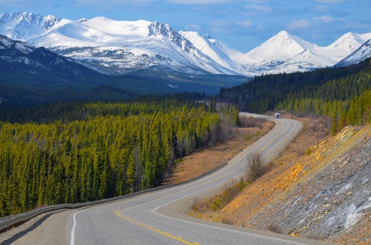 The Alaska Highway winds in amongst trees and mountains in the Yukon Territory, Canada