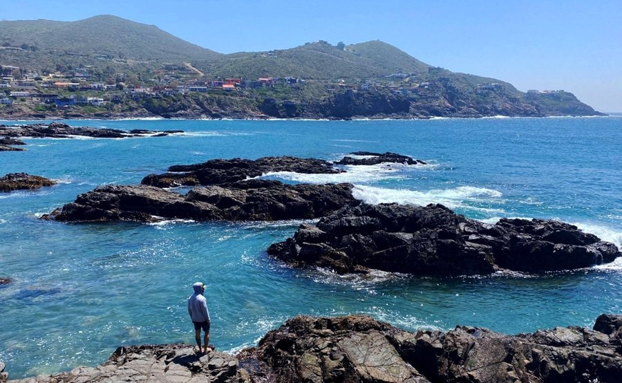 View of a man looking at the rocky coastline in Ensenada