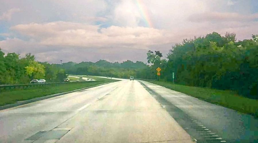 View of a not so busy highway in Puerto Rico and a rainbow on the sky
