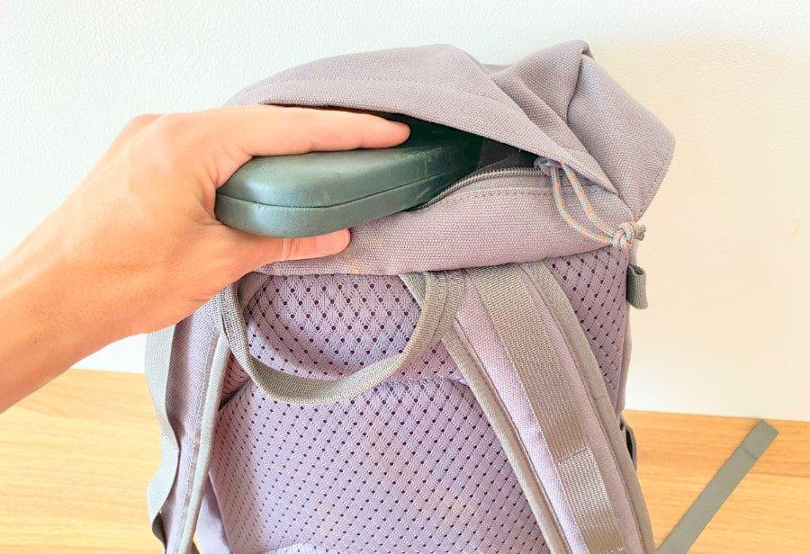 View of a hand inserting a glasses case into the top pocket of the Salkan daypack