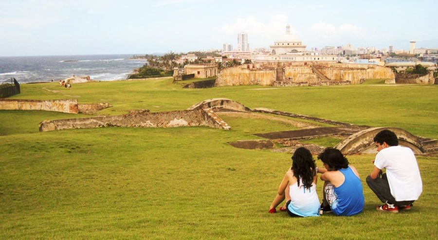 View of three people sitting on a grass and the San Cristobal Castle from afar