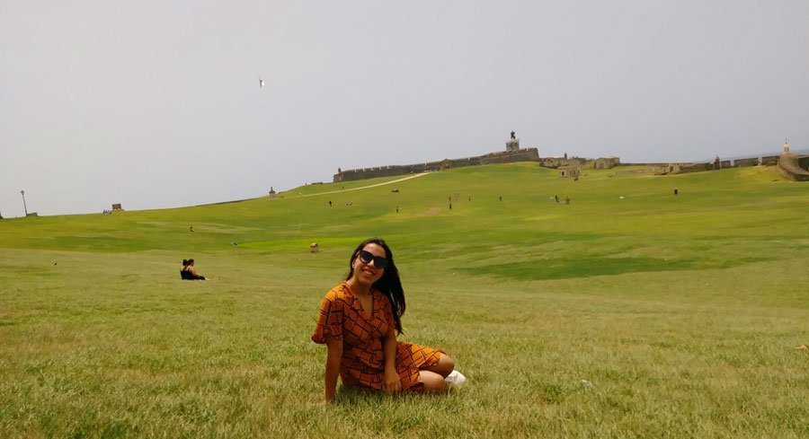 View of the author sitting in a green grass and the San Felipe del Moro on the background