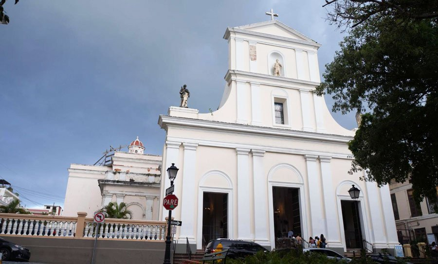 View of the San Juan Cathedral from the outside and some people going inside the church