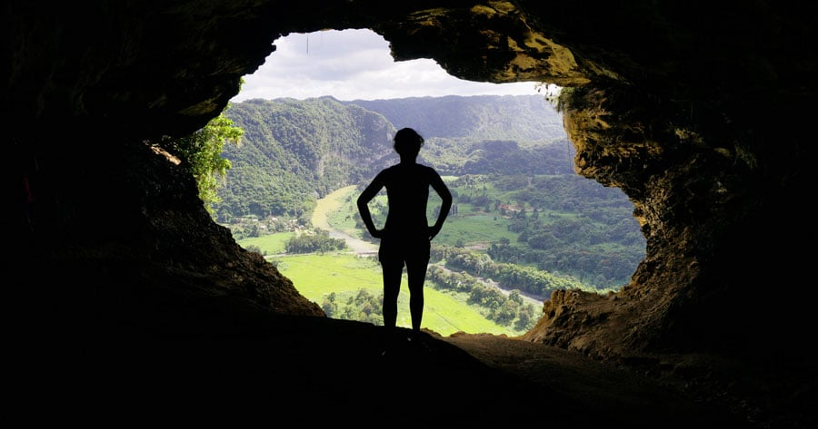 View of a person in Cueva Ventana enjoying the overlooking view of the countryside