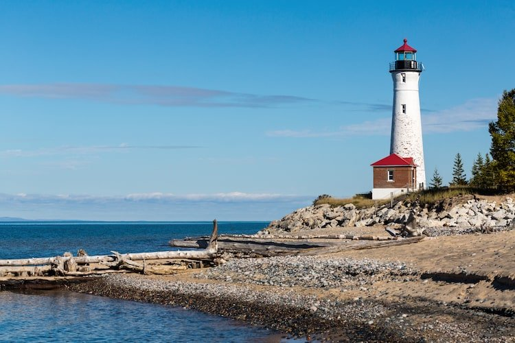 Red and White sheringham Point Lighthouse stands among blue water and waves on Vancouver Island, Canada
