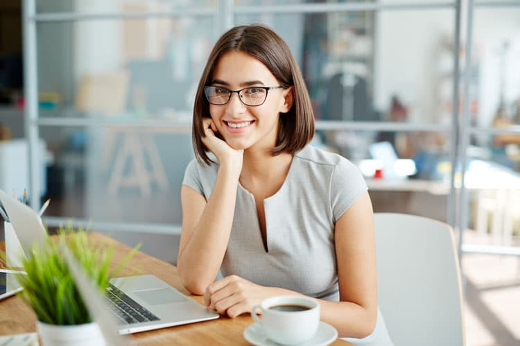 smiling woman sitting with laptop and cup of coffee