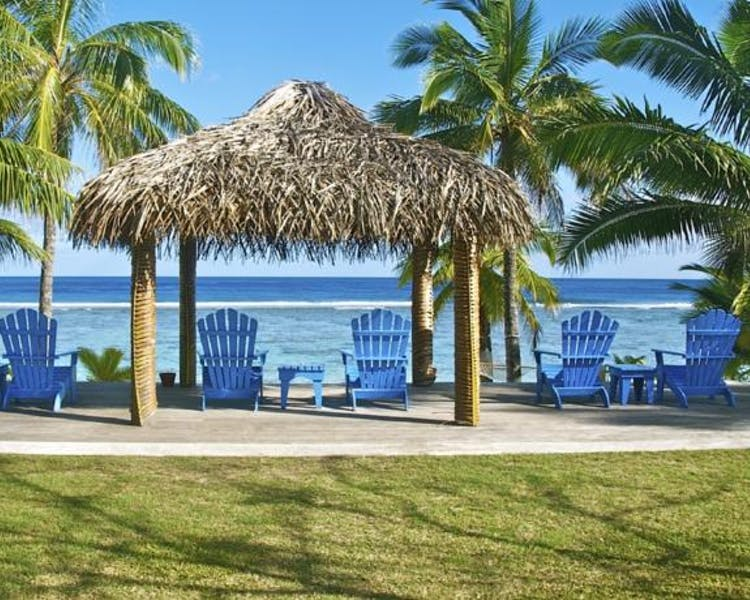 blue beach chairs beneath a hut with palm trees on the surroundings in Rarotonga Cook Islands