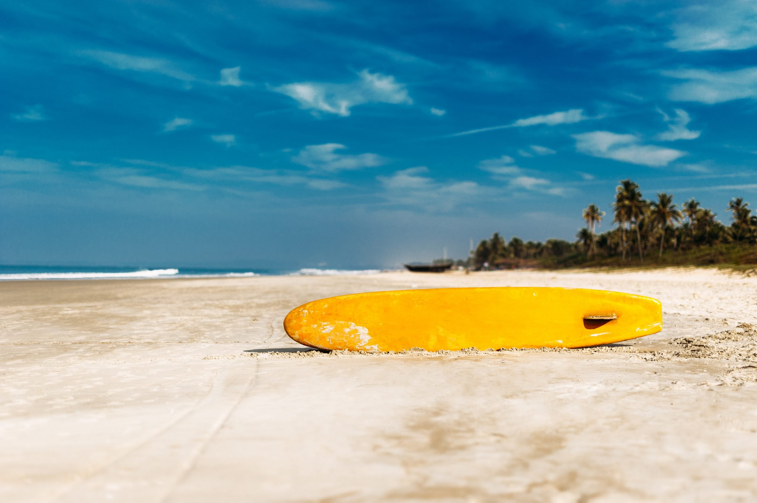 Surfboard on a tropical beach overlooking the ocean, blue sky background. Arugam Bay Sri Lanka, a top thing to do in Sri Lanka