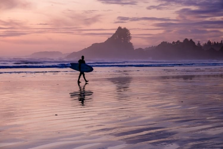 A person goes surfing in Tofino, Vancouver Island with a pink and purple sky