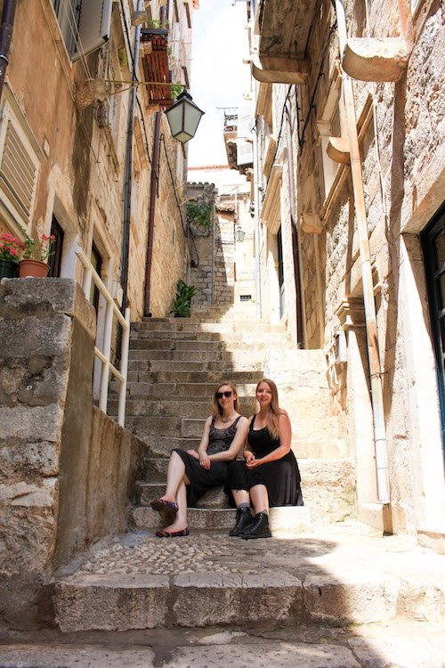 Taylor and a friend sit on steps in the old town of Dubrovnik