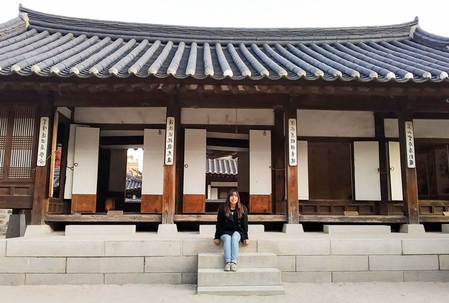 View of the author sitting in front of a Traditonal House in South Korea