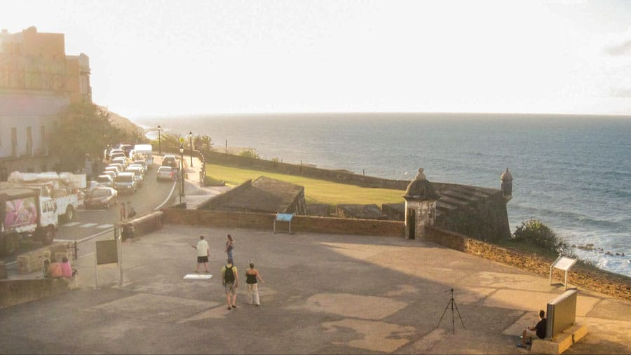 View of people walking near the sea and a traffic jam on the road