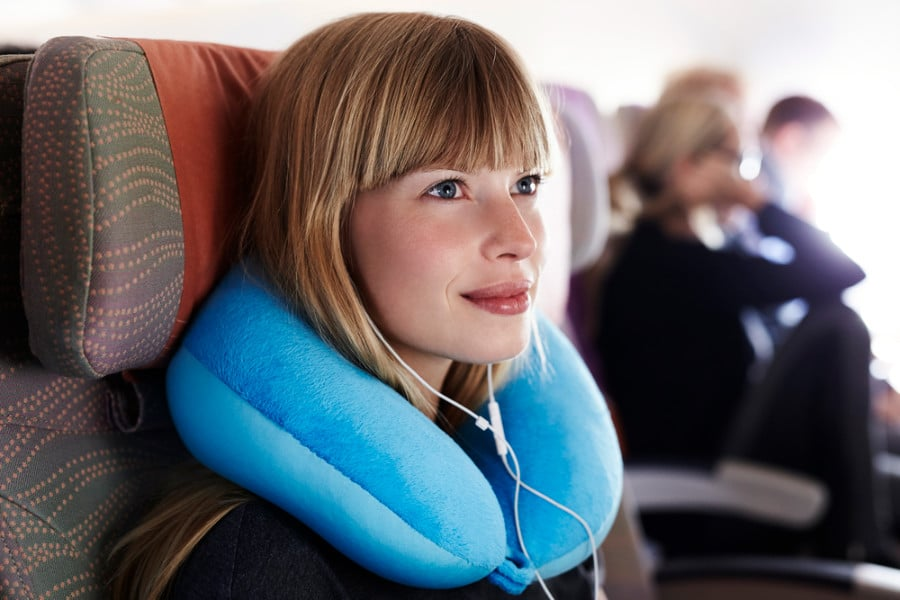 Photo of woman with travel neck pillow on airplane