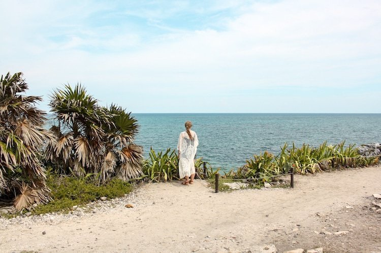 Taylor stands facing the ocean with palm trees around at the Tulum Ruins in Mexico