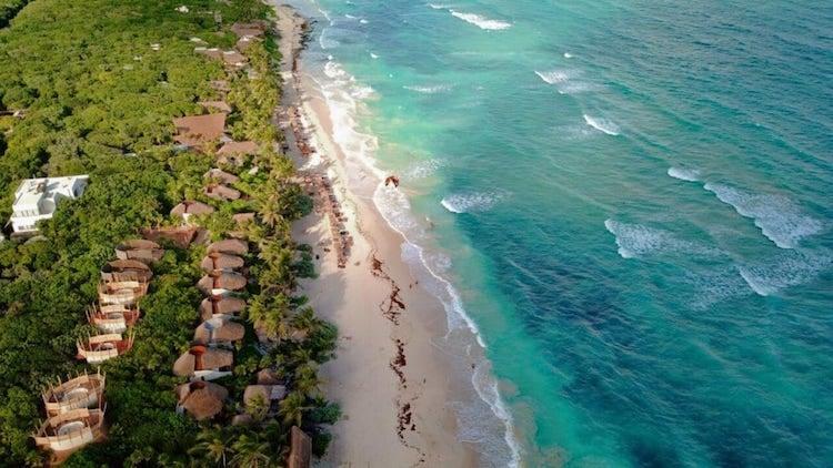 An aerial shot of Tulum's south beach, where the water meets the beach and the beach meets jungle.