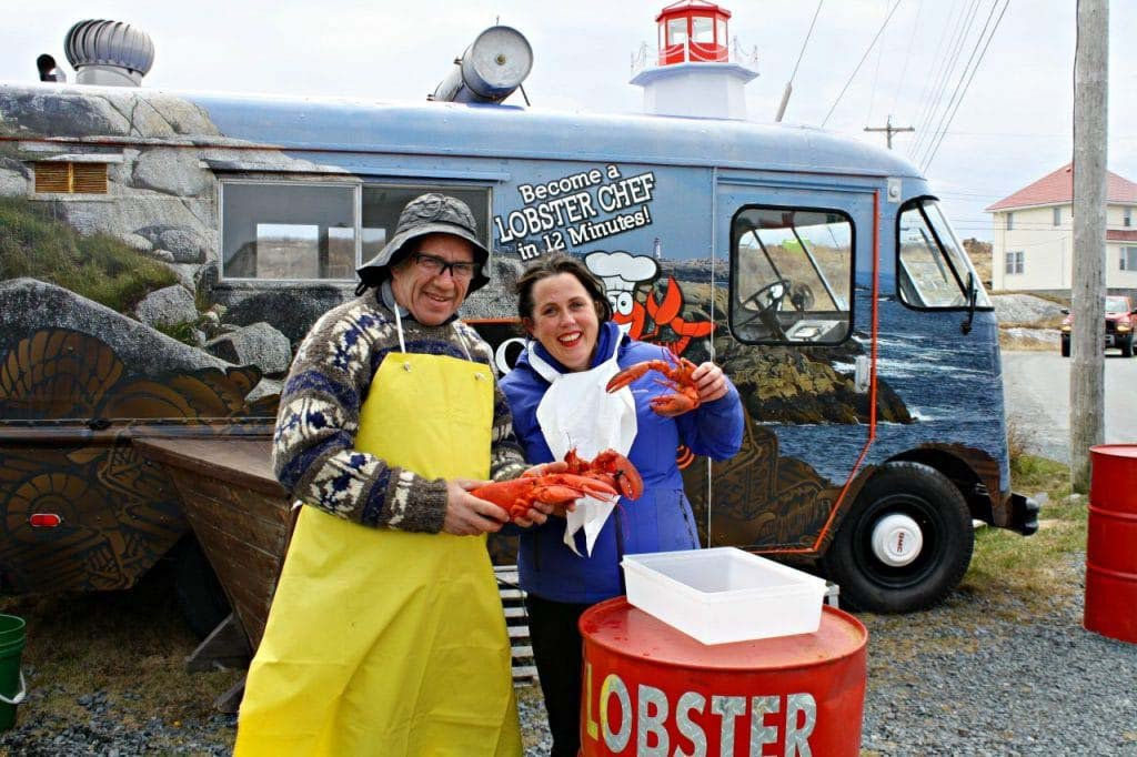 man and woman posed with lobsters with van on background at Peggy's Cove Nova Scotia