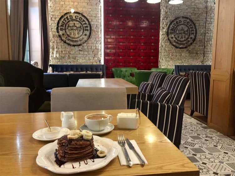 coffee shop interior with pancakes and coffee on the table and striped sofas