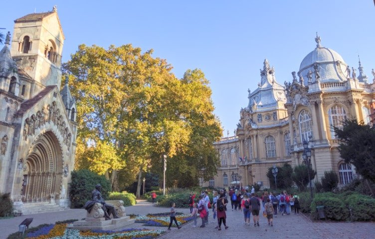 People walking on the grounds in front of Vajdahunyad Castle in the City Park of Budapest