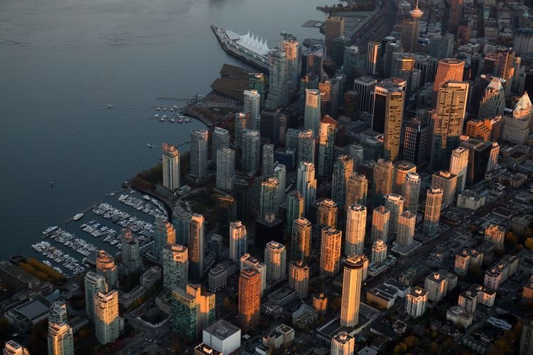 An aerial view of downtown Vancouver Canada, with skyscrapers and the harbor
