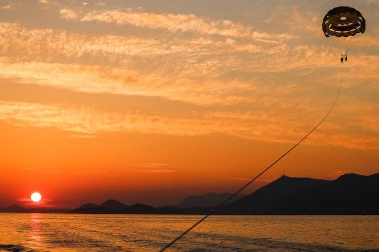 Two people hang from a balloon while parasailing in Cavtat, Croatia at sunset