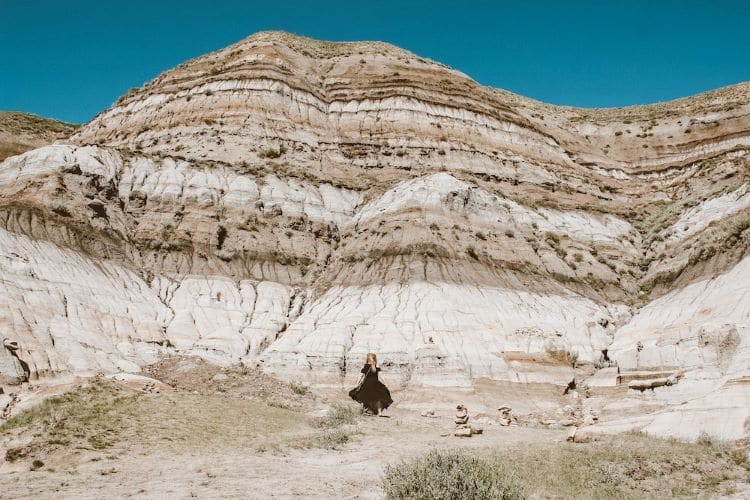 Taylor stands in front of layers of settled rock in Drumheller, Alberta Canada