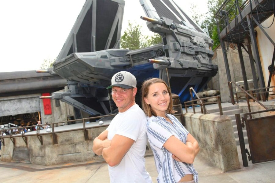 The author and her husband posing in Star Wars: Galaxy's Edge at Disney's Hollywood Studio, with Star Wars exhibit in background