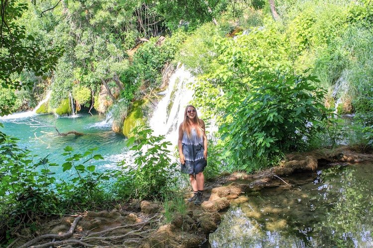 Taylor stands in front of a turquoise lake and waterfall at Krka National Park, Croatia