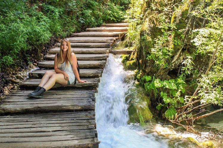 Taylor sits on wooden steps over a waterfall in Plitvice Lakes National Park, Croatia