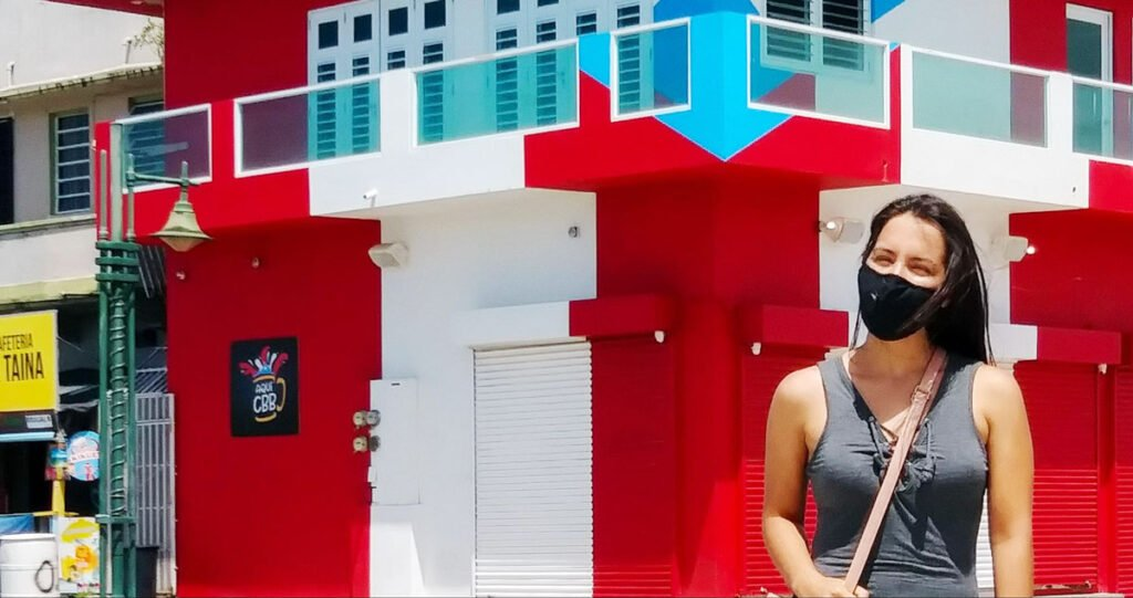 View of the author and a house painted with the Puerto Rico flag on her background