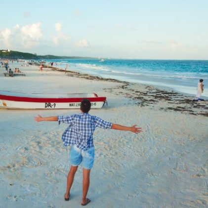 Man with arms out on beach in Tulum