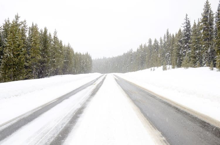 Snow covers the ground on the highway surrouned by trees in rural Canada