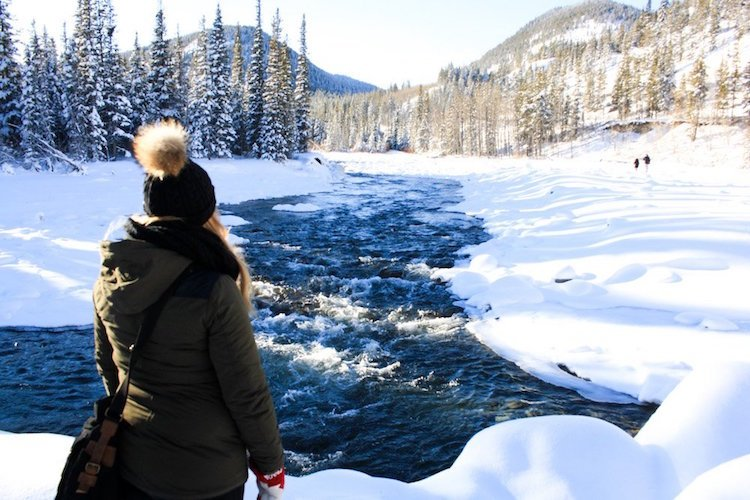 Taylor stands with her back to the camera as she looks out over a rushing river surrounded by powdery white snow, trees, and mountains in Kananaskis, Alberta