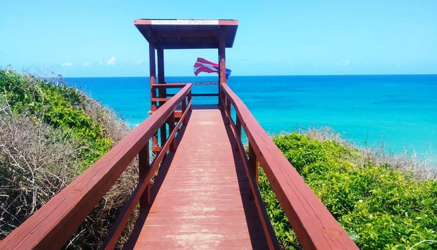 View of a wooden footwalk with a view of the ocean and the flag of Puerto Rico at the end