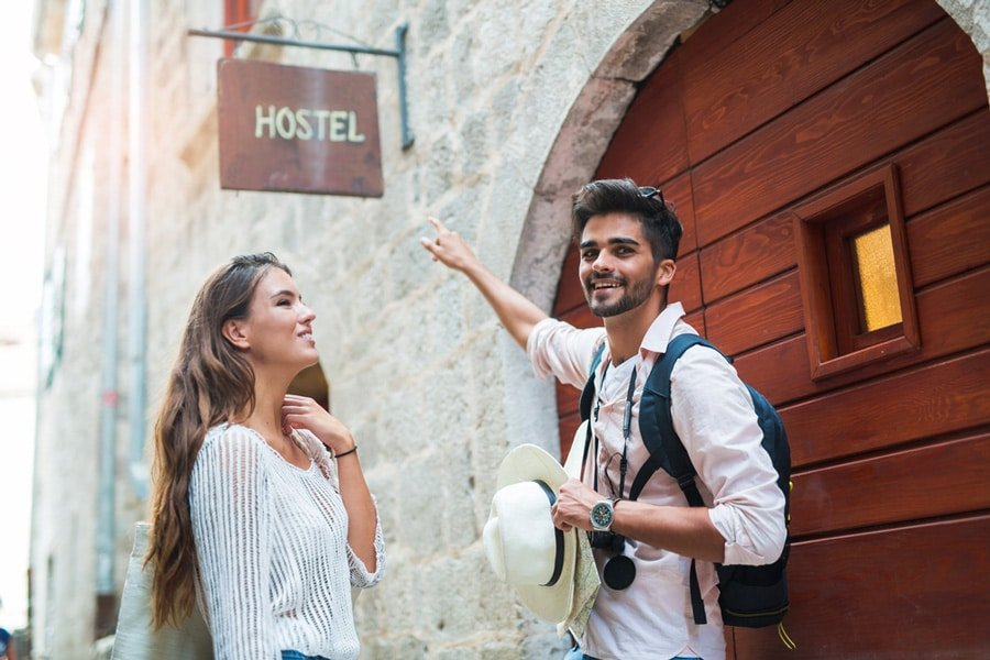 View of a couple pointing on a Hostel sign