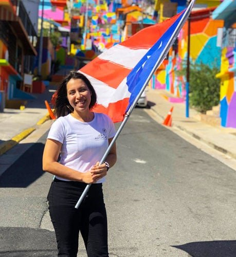 View of the author holding a flag in the colorful street of Yauco