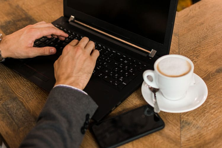 man on laptopn with white cup of latte