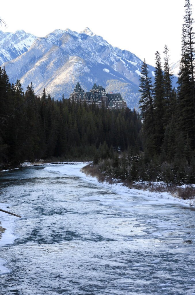 Banff Springs Hotel against a background of the Canadian Rocky Mountains with trees and a river in the foreground