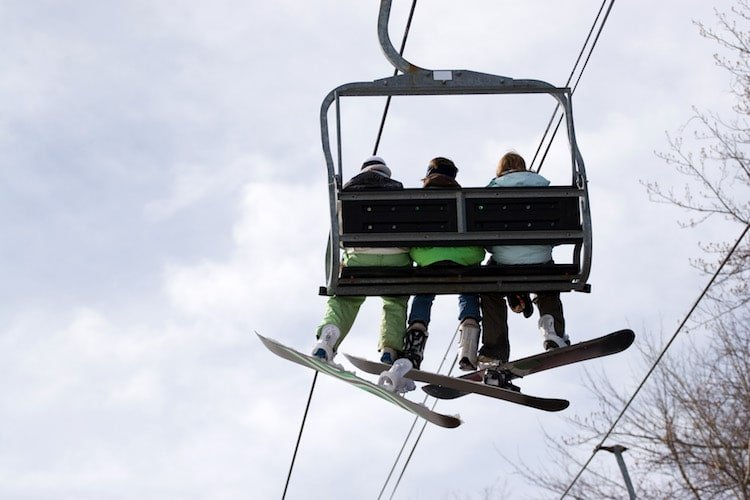 Three snowboarder friends ride the ski lift to the top of the mountain.