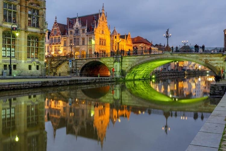 Ghent, Belgium at night. Photo of the river, a bridge, and old buildings all lit up.