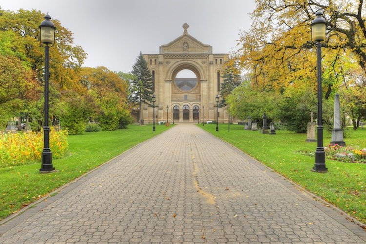 A walkway leads up to the Saint Boniface Cathedral as the leaves change to fall colors around it in Winnipeg Manitoba.