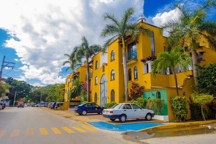 Cars sit in front of a yellow hotel in Playa del Carmen, Mexico