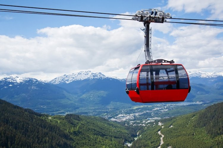 Red car of the aerial tramway connecting two high peaks at Whistler Mountain in British Columbia, Canada with blue sky and white clouds